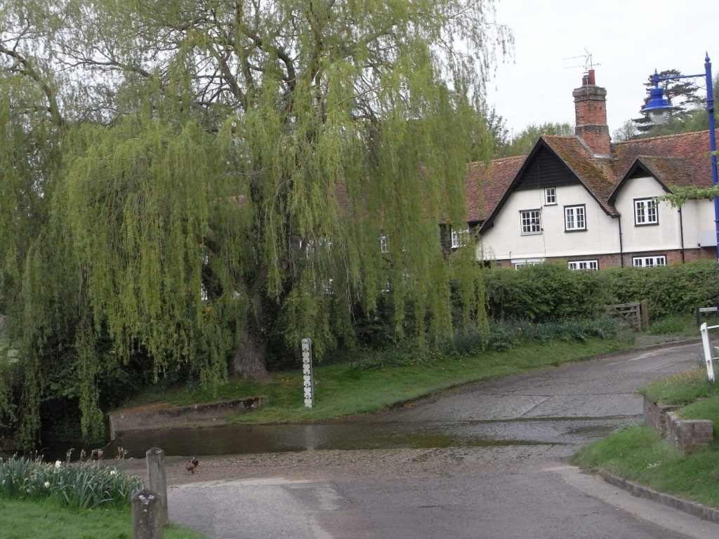 A house at a crossroads with a weeping willow tree infront of the house
