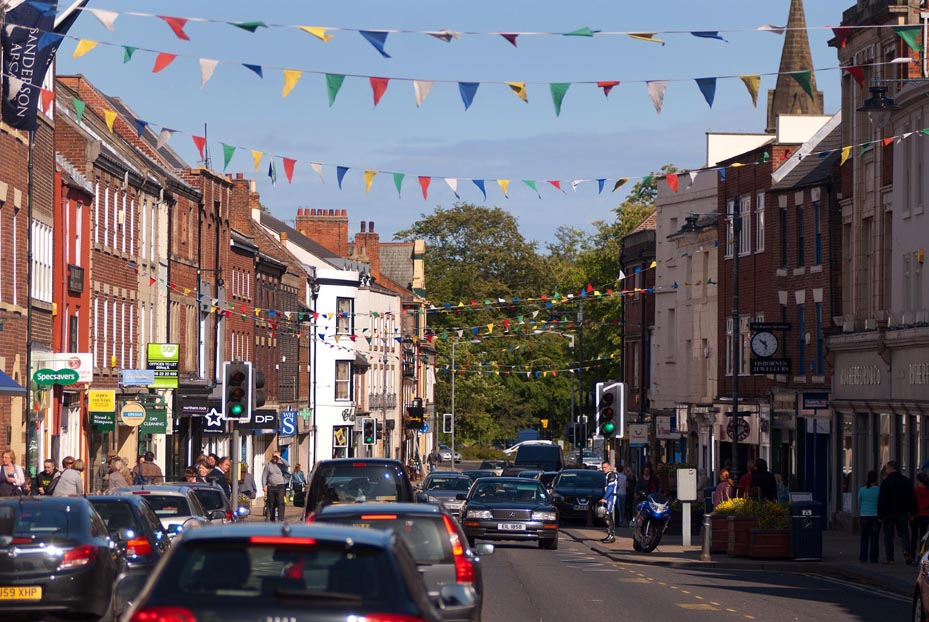 Image shows Morpeth's High Street on a sunny day with bunting flying overhead across the road.