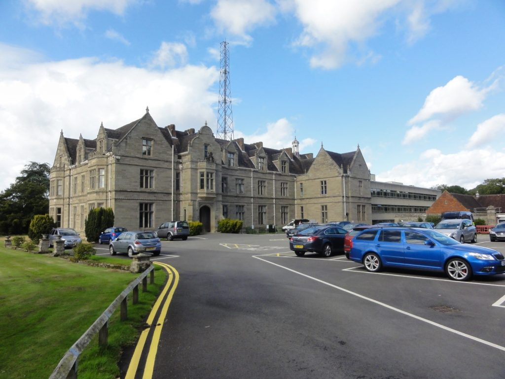 A photo of a large house with a car park in front of it