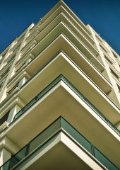 A photolooking up at the corner of a building with many balconies